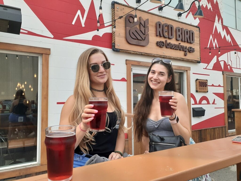 two women enjoying beers at the outdoor patio at Red Bird Brewing in Kelowna, BC
