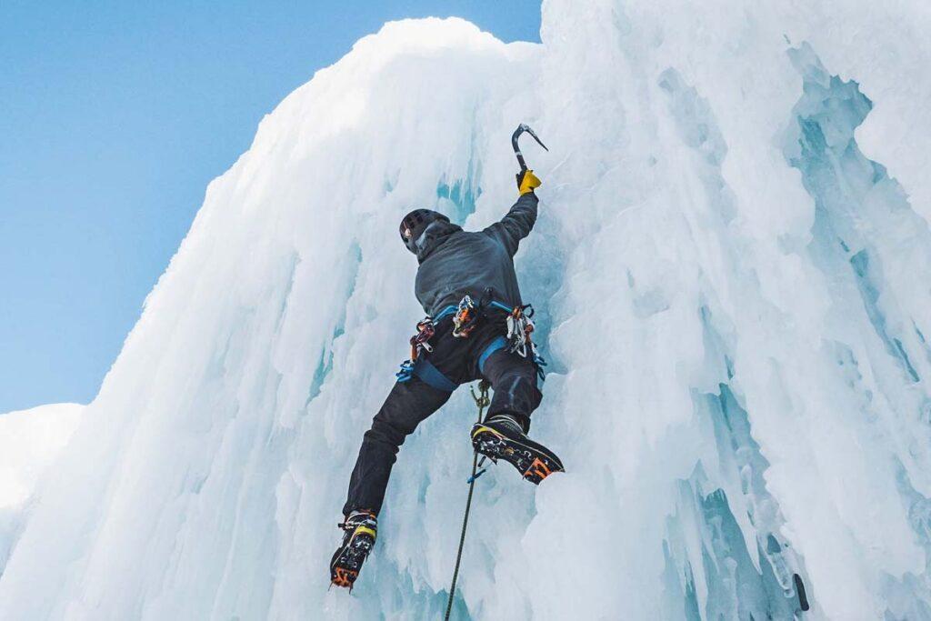 An ice climber climbs a frozen waterfall in Golden, BC