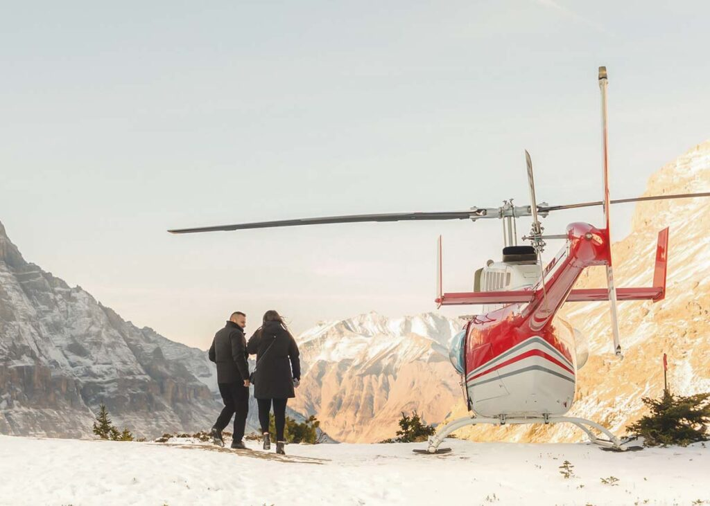 A helicopter sits on a mountain in Banff National Park in winter with two people