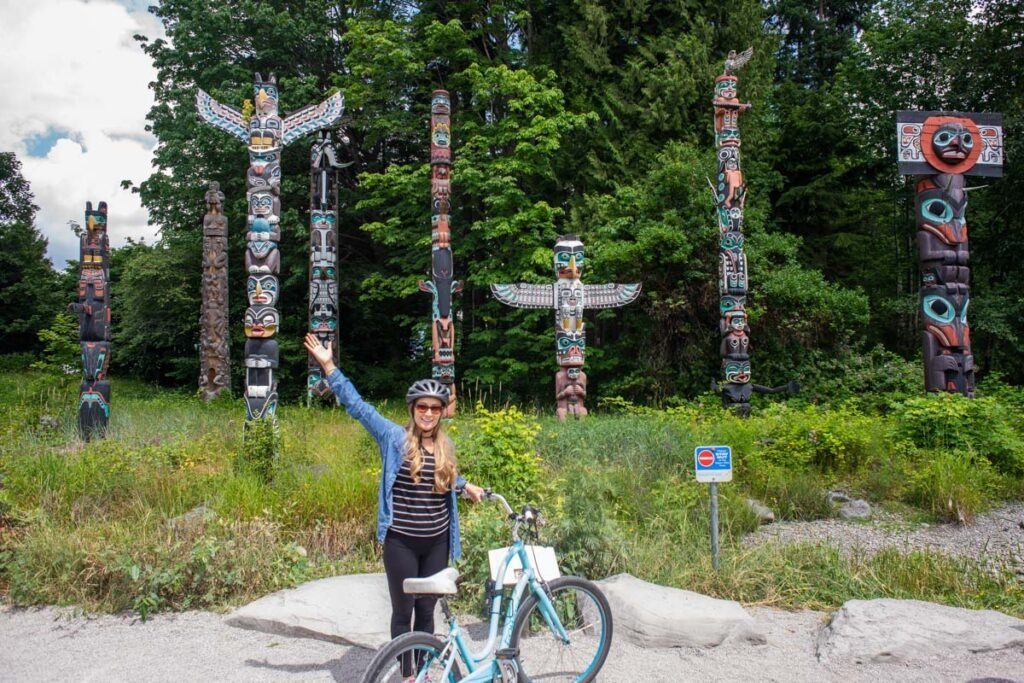 A lady poses for a photo in front of the Stanley Park Totem Poles