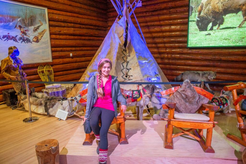 A lady poses for a photo with a display at the Buffalo Nations Museum, Banff