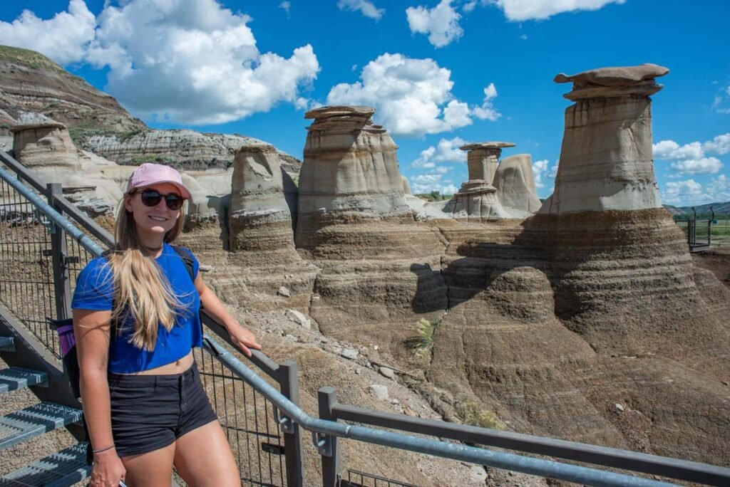 Bailey from Destinationless Travel poses with a hoodoos in Drumheller