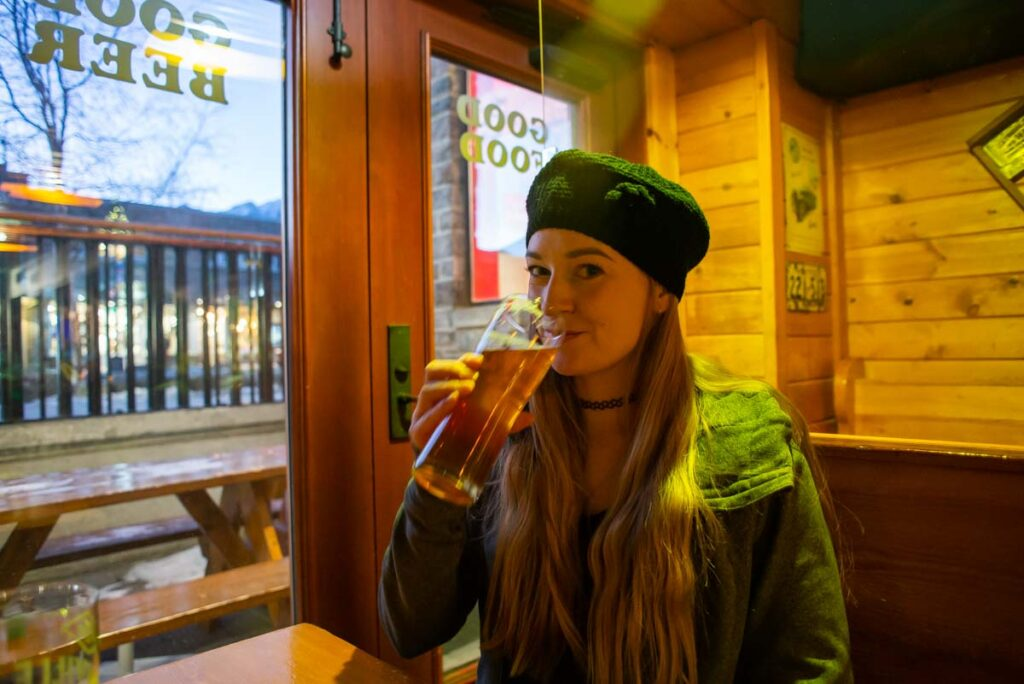 A lady drinks a beer at Tommy's Neighborhood Pub