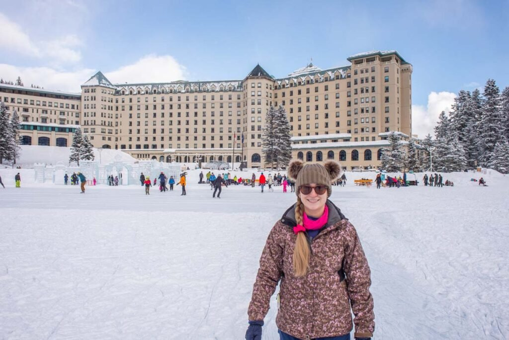 A lady stands in front fo the Fairmont Chateau Lake Louise