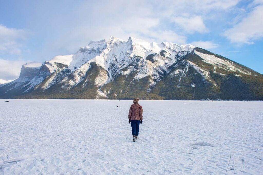 A lady walk's along a frozen Lake Minnewanka in Banff