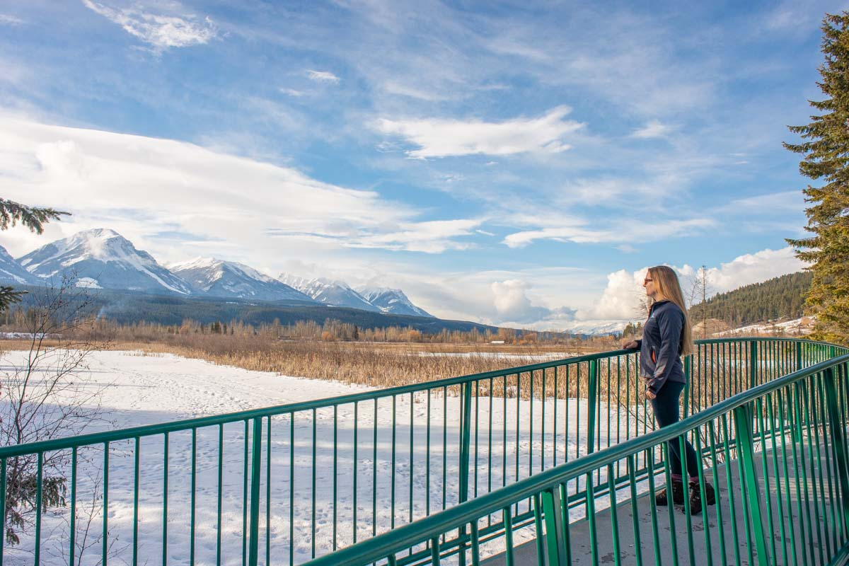 A lady stands on a bridge at Beaver Lakes in Golden, BC in winter