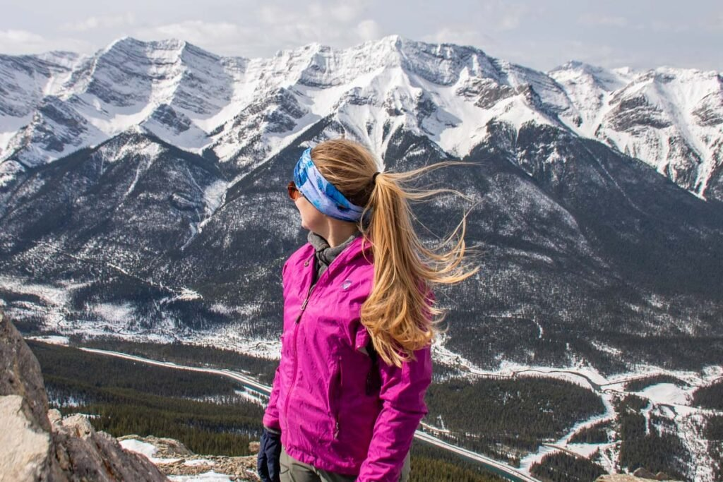 Bailey stands on a mountain in essential gear for the Canadian Rockies