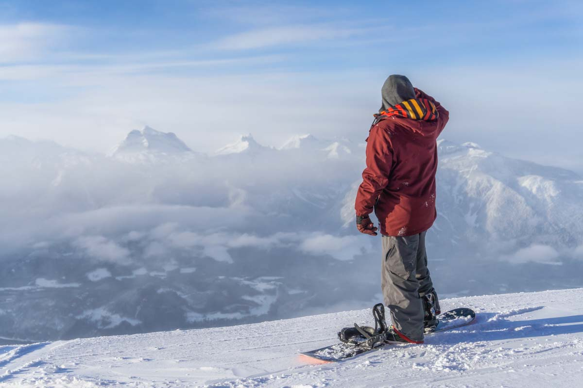 A snowboarder stands at the top of Revelstoke Mountain Resort in BC, Canada during winter
