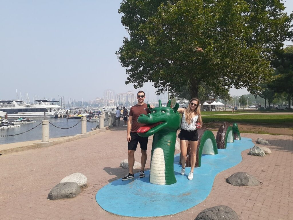 a couple taking a photo with the famous ogopogo statue in downtown Kelowna
